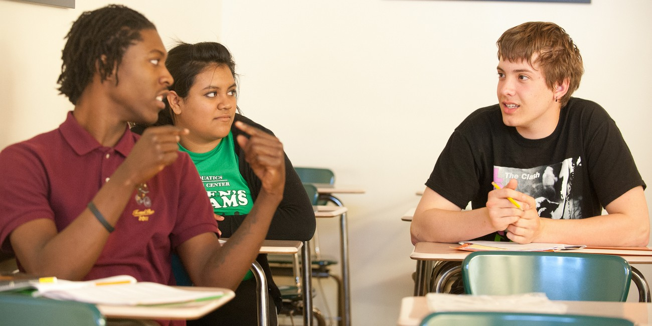 Students discuss an assignment in class.